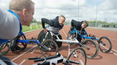 4K Smiling disabled athletes in racing wheelchairs chatting at race track Stock Footage