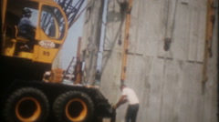 Large crane lifts and holds concrete panels-3402 vintage film home movie Stock Footage