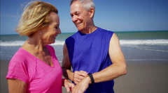 Senior Caucasian couple using sport watch technology on the beach Stock Footage