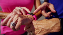 Hands of retired Caucasian couple using wearable technology sport watches Stock Footage