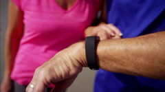 Hands of Caucasian seniors using sport watches to keep fit Stock Footage