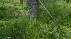 Worker gardener man mowing trimming grass with fuel scythe trimmer. Close-up. - stock footage