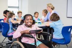 Disabled schoolgirl using digital tablet in classroom at school - stock photo