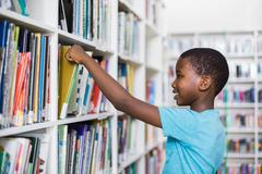 Schoolboy selecting a book from bookcase in library at school Stock Photos