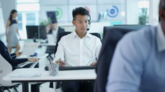 4K Friendly customer service operator talking to customer in busy call centre - stock footage