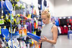 Woman shopping sports equipment in sportswear store. Stock Photos