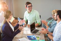 Coworkers applauding a colleague after presentation in the office Stock Photos