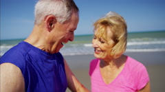 Active senior Caucasian couple after successful workout on the beach Arkistovideo