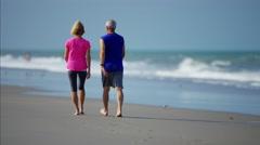 Healthy senior Caucasian couple enjoying exercise on the beach Stock Footage
