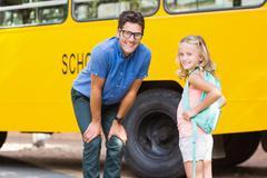 Portrait of smiling teacher and schoolgirl standing in front of school bus - stock photo
