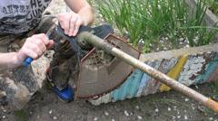 Man fix trimmer in garden. Male hands repairing mower trimmer blades edges - stock footage