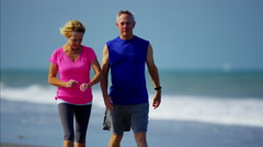 Happy mature Caucasian couple keeping healthy on the ocean beach Stock Footage