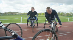 4K Smiling disabled athletes chatting & warming up at race track - stock footage