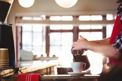 Mid section of waiter pouring a cup of coffee on counter - stock photo