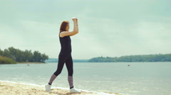 beautiful red-haired girl doing exercises on the river - stock footage