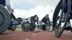 4K Smiling disabled athletes chatting & warming up at race track Stock Footage
