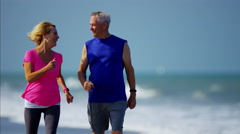 Senior Caucasian couple using fitness activity sport watch on the beach Stock Footage