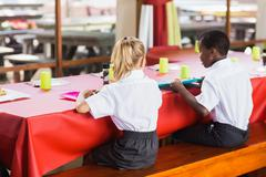 Rear view of boy and girl in school uniforms having lunch in school cafeteria Stock Photos