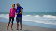 Retired Caucasian couple wearing sport watch to exercise on the beach Stock Footage
