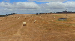 AERIAL: Flying across the width of big golden endless field of bales of haystack Stock Footage