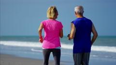 Smiling Caucasian seniors enjoying running on the ocean beach Stock Footage
