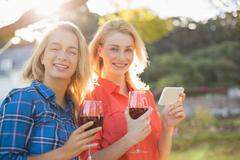 Smiling beautiful women holding glasses of red wine and mobile phone in park Stock Photos