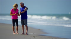 Senior Caucasian couple enjoying exercise on the ocean beach Stock Footage