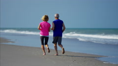 Caucasian seniors enjoying running on the ocean beach Stock Footage