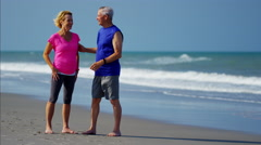 Retired Caucasian couple using wearable technology to exercise on the beach Stock Footage