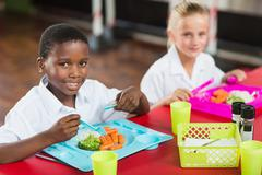 Portrait of boy and girl in school uniforms having lunch in school cafeteria Stock Photos