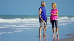 Healthy senior Caucasian couple enjoying fitness activity on the beach Stock Footage