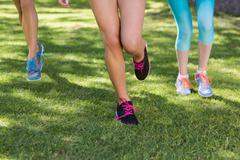Female athlete feet running on grass in park Stock Photos