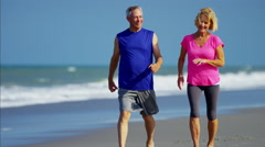 Active retired Caucasian couple enjoying exercise on the beach Stock Footage