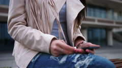 Young smiling brunette woman, wearing blue jeans and white jacket, putting on Stock Footage