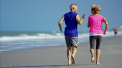 Active retired Caucasian couple enjoying running on the beach Stock Footage