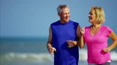 Active retired Caucasian couple enjoying jogging on the ocean beach Stock Footage