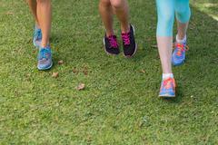 Female athlete feet running on grass in park - stock photo