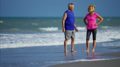 Smiling senior Caucasian couple enjoying fitness activity on the beach Stock Footage