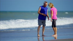 Senior Caucasian couple having fun on the ocean beach Stock Footage