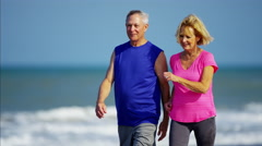 Caucasian seniors keeping fit on the beach Stock Footage