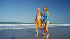 Mature Caucasian couple wearing swimsuits having fun on beach vacation Stock Footage