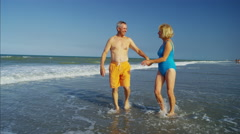 Happy retired Caucasian couple in swimwear having fun on the beach holiday Stock Footage