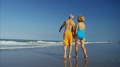 Senior Caucasian couple in swimsuits relaxing on the beach Stock Footage