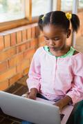 Schoolgirl sitting on stairs and using laptop at school - stock photo