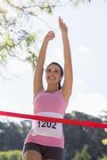 Cheerful winner female athlete crossing finish line in park Stock Photos
