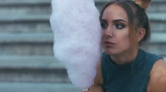 Young woman eating sweetened cotton candy, smiling and doing funny faces - stock footage