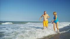 Healthy senior Caucasian couple in swimwear running beside the ocean Stock Footage