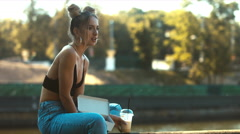 Portrait of young attractive blonde girl in jeans drinking milkshake in the park - stock footage