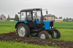 Tractor operator plows the site in rain Stock Photos