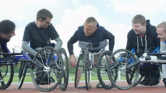 4K Smiling disabled athletics team in racing wheelchairs chatting at race track  Stock Footage